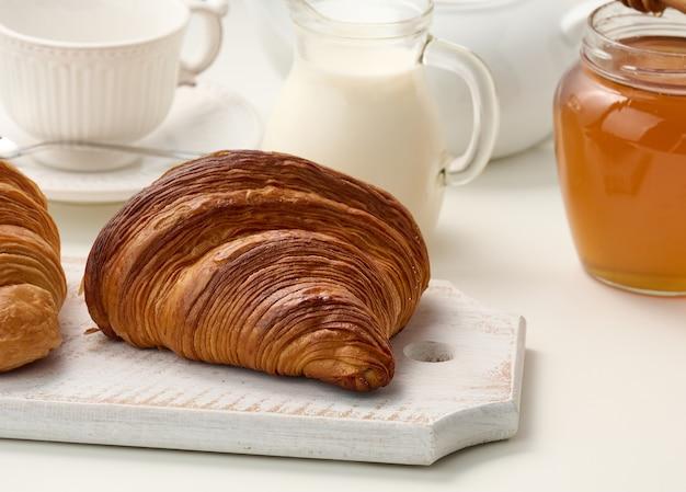 Pieczony chrupiący croissant na drewnianej desce, biały ceramiczny napar i filiżanka na białym stole. śniadanie, z bliska