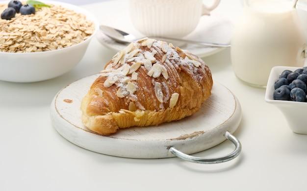 Pieczony chrupiący croissant na drewnianej desce, talerz z jagodami, biały ceramiczny napar i filiżanka na białym stole. śniadanie