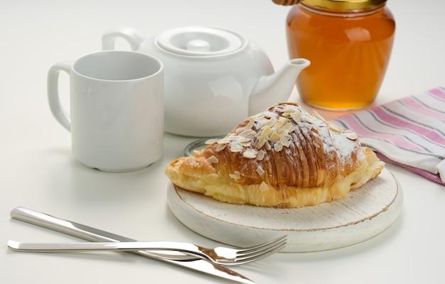 Pieczony chrupiący croissant posypany cukrem pudrem i płatkami migdałów na drewnianej desce, biały ceramiczny wywar i filiżanka na białym stole. śniadanie