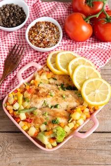 Pieczony domowy kurczak z pieca z warzywami i cytryną. zastawa stołowa. widok z góry.