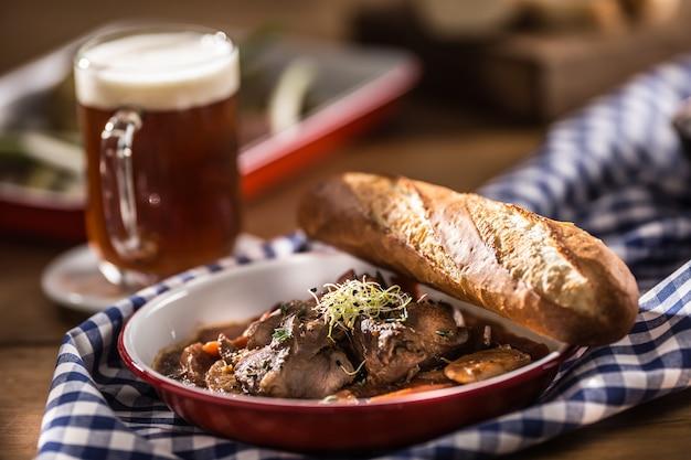 Pieczony dzik z pieczarkami marchewkowymi, bagietką i lanym piwem.