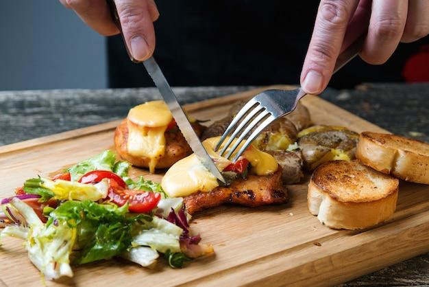 Pieczony filet z kurczaka z serem, pieczonymi ziemniakami i surówką na drewnianej desce. szybki przepis na danie obiadowe. zdrowe domowe jedzenie. smaczny obiad z filetem z kurczaka.