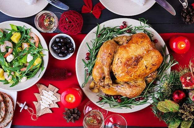 Pieczony indyk. obiad świąteczny. świąteczny stół jest podawany z indykiem, ozdobionym jasnym świecidełkiem i świecami. smażony kurczak, stół. rodzinny obiad. widok z góry