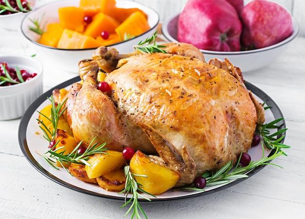 Pieczony indyk przyozdobiony żurawiną na stole w stylu rustykalnym ozdobiony jesiennym liściem. święto dziękczynienia. pieczony kurczak.
