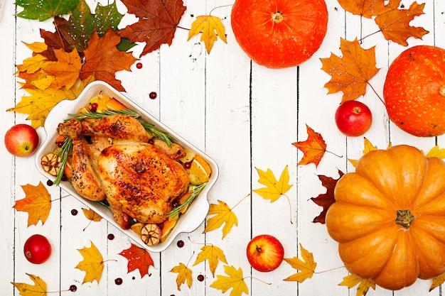 Pieczony indyk przyozdobiony żurawiną na stole w stylu rustykalnym ozdobionym dyniami, pomarańczą, jabłkami i jesiennym liściem