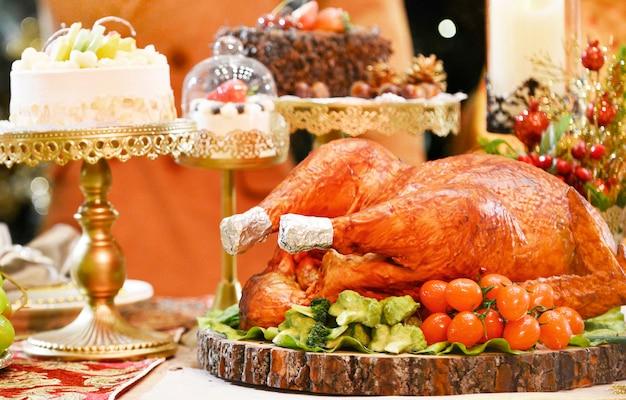 Pieczony indyk. stół podawany z indykiem w świątecznej kolacji, ozdobiony świecami.