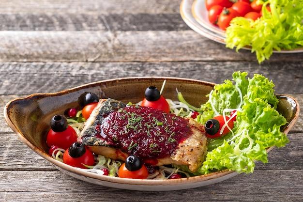 Pieczony jesiotr pod sosem żurawinowym z pomidorami i oliwkami na talerzu.