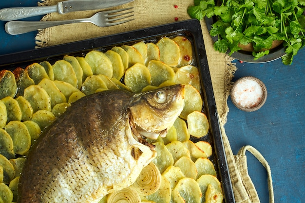 Pieczony karp, cała ryba z pieca z pokrojonymi ziemniakami na dużej tacy