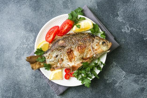 Pieczony karp ryba z warzywami i przyprawami na talerzu na ciemnym stole z kopią miejsca.