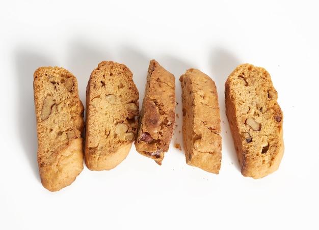 Pieczony kawałek włoskich biscotti migdałowych, ciasteczka cantuccini, tradycyjne włoskie święta bożego narodzenia, suche ciasteczka noworoczne. pieczenie na białym tle, widok z góry