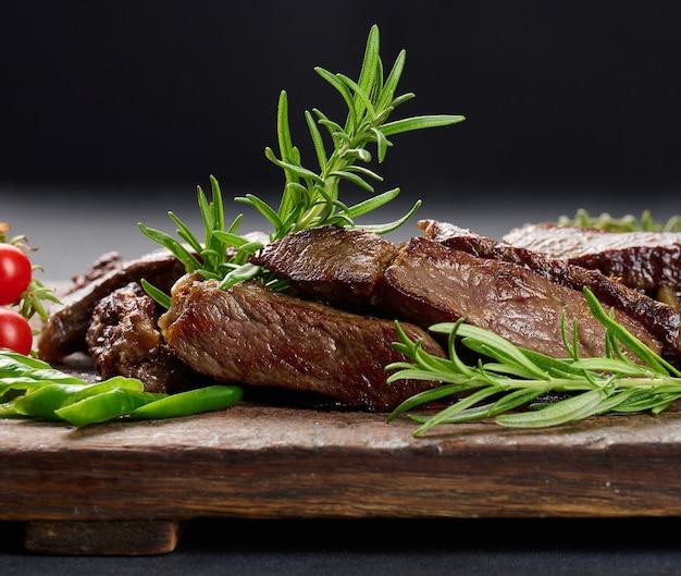 Pieczony kawałek wołowiny ribeye pokrojony na kawałki na brązowej desce do krojenia w stylu vintage, rzadkie wysmażenie. apetyczny stek