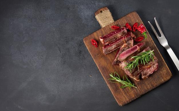 Pieczony kawałek wołowiny ribeye pokrojony na kawałki na brązowej desce do krojenia w stylu vintage, rzadkie wysmażenie. pyszny stek, kopia przestrzeń