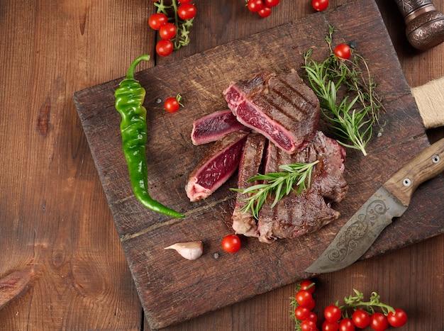 Pieczony kawałek wołowiny ribeye pokrojony na kawałki na brązowej desce do krojenia w stylu vintage, rzadkie wysmażenie. pyszny stek, widok z góry