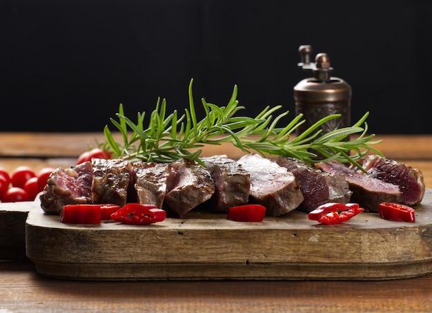Pieczony kawałek wołowiny ribeye pokrojony na kawałki na brązowej desce do krojenia w stylu vintage, rzadkie wysmażenie. pyszny stek, z bliska