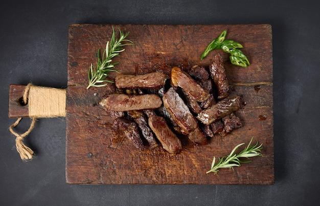 Pieczony kawałek wołowiny ribeye pokrojony na kawałki na starej brązowej desce do krojenia. bardzo dobrze. apetyczny stek, widok z góry