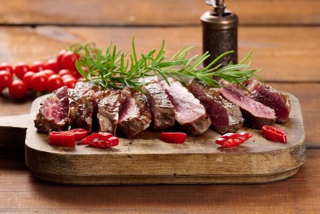 Pieczony kawałek wołowiny ribeye pokrojony na kawałki na starej brązowej desce do krojenia. bardzo dobrze. apetyczny stek