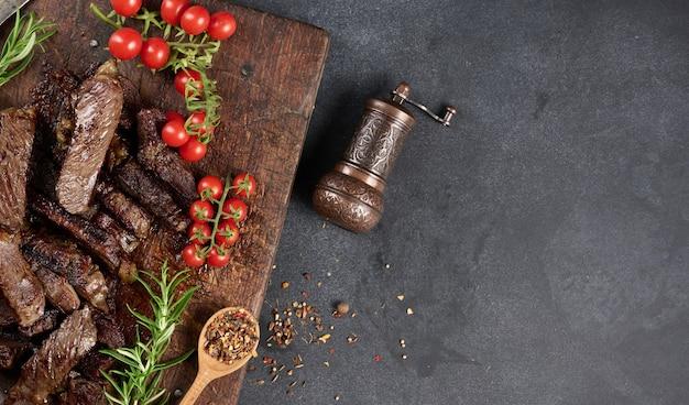 Pieczony kawałek wołowiny ribeye pokrojony na kawałki na starej brązowej desce do krojenia. pyszny stek, kopia przestrzeń