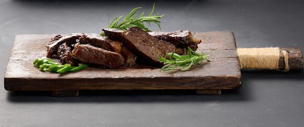 Pieczony kawałek wołowiny ribeye pokrojony na kawałki na starej brązowej desce do krojenia. pyszny stek, z bliska