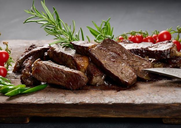 Pieczony kawałek wołowiny ribeye pokrojony na kawałki na starej brązowej desce do krojenia, rzadkie wysmażenie. apetyczny stek