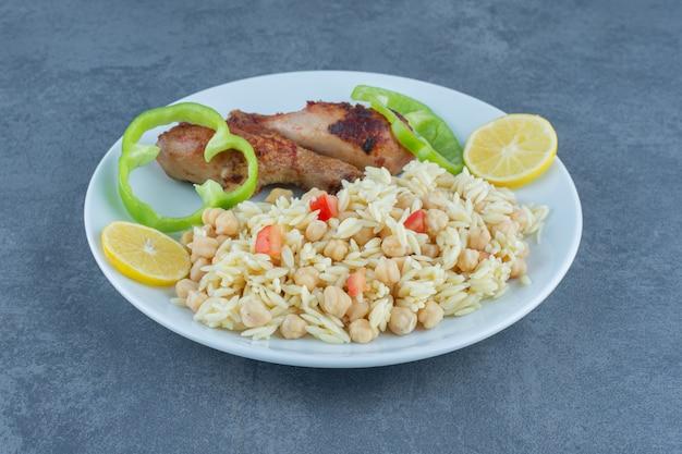 Pieczony kurczak i ryż z ciecierzycą na białym talerzu.