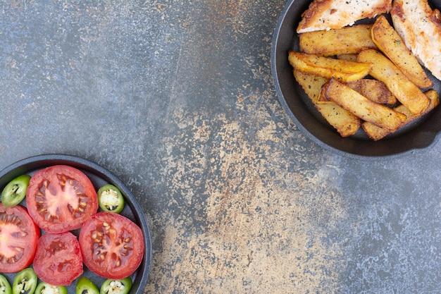 Pieczony kurczak i ziemniaki na patelni z talerzem warzyw. zdjęcie wysokiej jakości