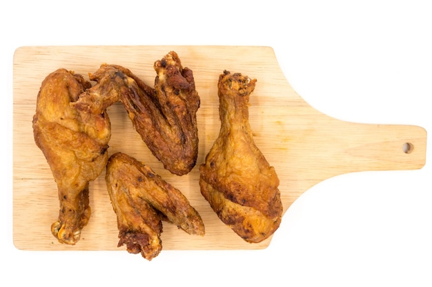 Pieczony kurczak iść na piechotę i uskrzydla na drewnianej tacy nad białym tłem.