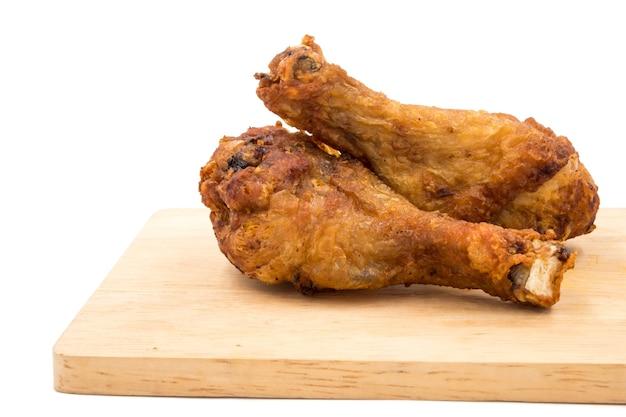 Pieczony kurczak iść na piechotę na drewnianej tacy nad białym tłem.