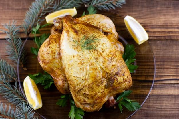Pieczony kurczak na drewnianym. świąteczny obiad na święta. gotowany kurczak w domu