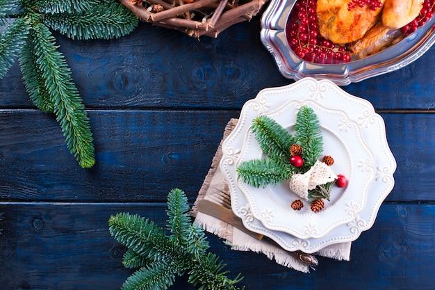 Pieczony kurczak na talerzu z czerwonymi jagodami. na niebieskim drewnianym stole z grabią