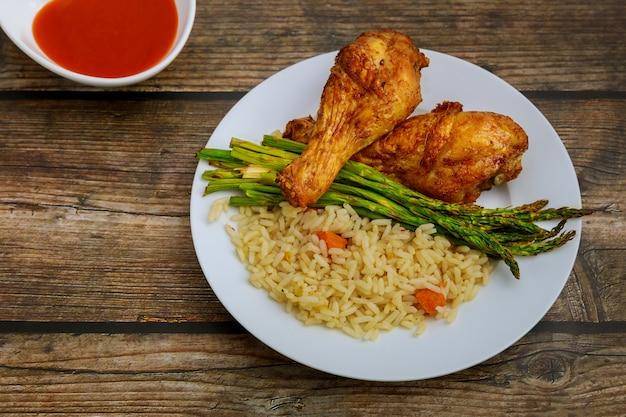 Pieczony kurczak pikantny podudzie z sałatką i sosem na podłoże drewniane. widok z góry..