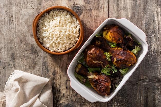 Pieczony kurczak tandoori z ryżem basmati na drewnianym stole. widok z góry.
