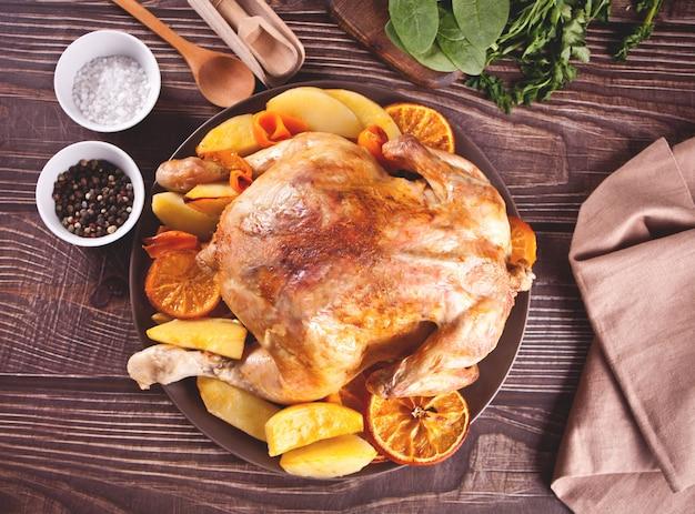 Pieczony kurczak w całości z pomarańczami i ziemniakami na talerzu.