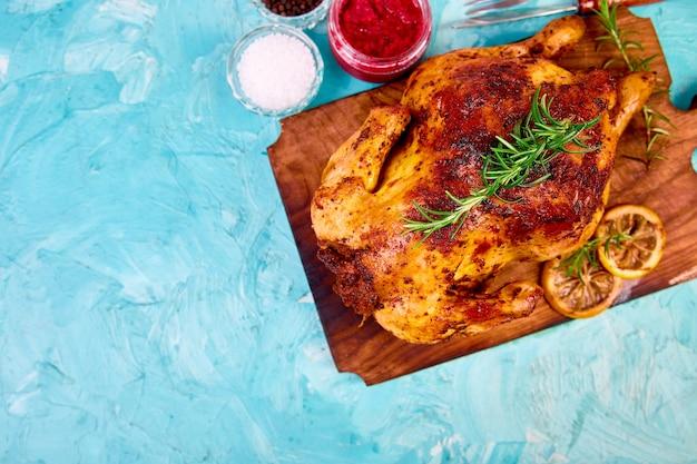 Pieczony kurczak w całości z sosami na desce na niebieskim tle.