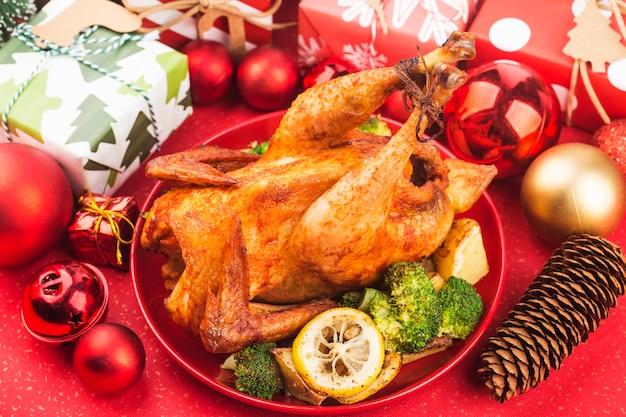 Pieczony kurczak w całości ze świątecznymi dekoracjami.