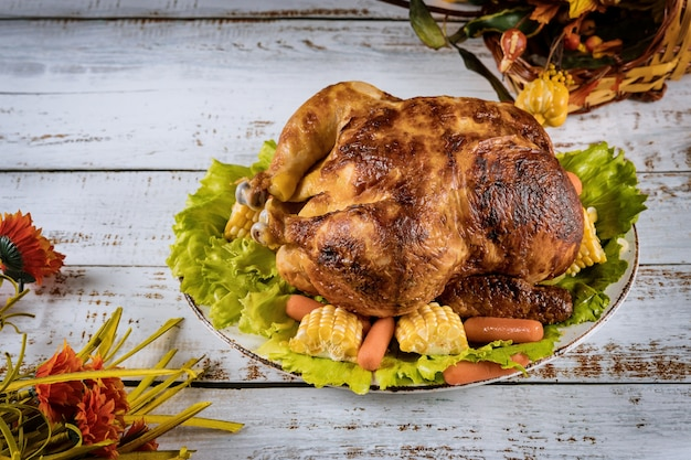 Pieczony kurczak w święto dziękczynienia stół na święto dziękczynienia podawany z dekorowanymi jasnymi jesiennymi liśćmi na stole.