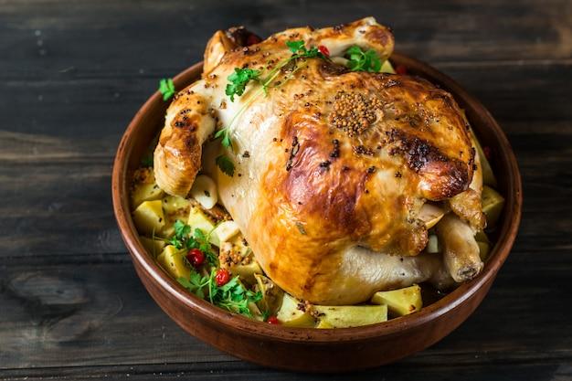 Pieczony kurczak z pieczarkami i ziemniakami w naczyniu do pieczenia na stole. pieczony indyk. chris
