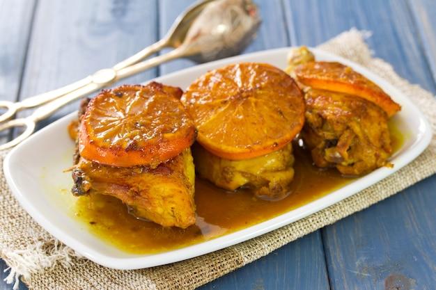 Pieczony kurczak z pomarańczami na białym naczyniu na błękitnym drewnie