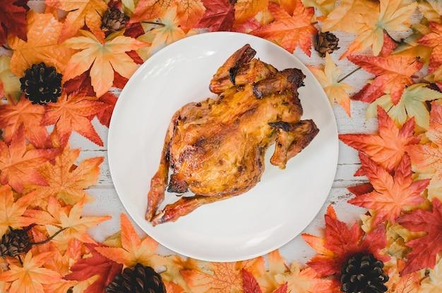 Pieczony kurczak z tłem jesieni i jesieni. fałszywy liść klonu na stole z drewna. koncepcja róg obfitości zbiorów i święto dziękczynienia.