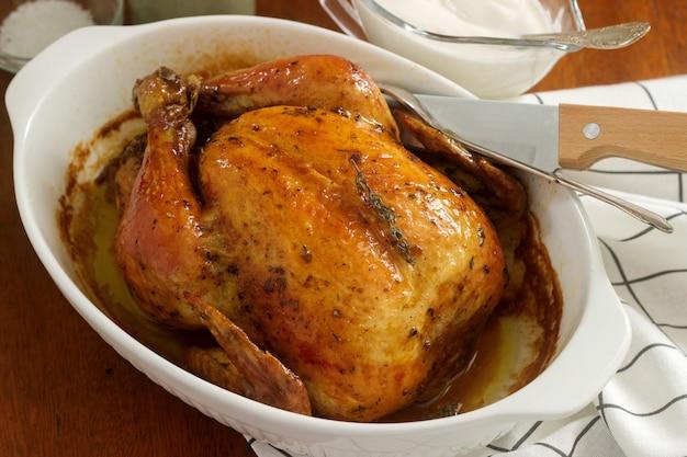 Pieczony kurczak z ziołami i czosnkiem, podawany z sosem śmietanowym. styl rustykalny.