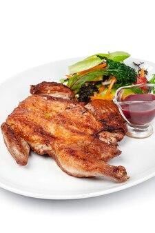 Pieczony kurczak ze skórką na białym tle z bliska
