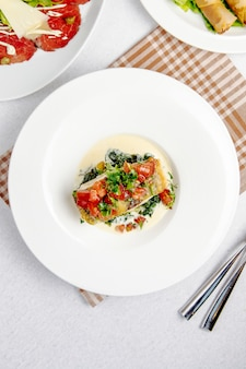 Pieczony labraks z pomidorami na białym talerzu