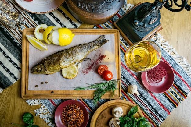 Pieczony labraks z przyprawami rybnymi, winem i surówką. pieczone owoce morza w restauracji zdrowe odżywianie