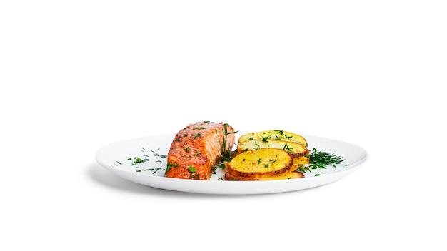 Pieczony łosoś i ziemniaki z ziołami na białym talerzu na białym tle