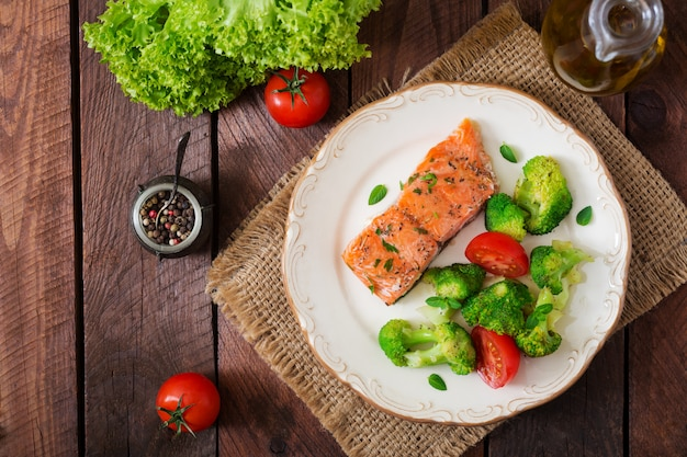 Pieczony łosoś rybny przyozdobiony brokułami i pomidorem. menu dietetyczne. menu rybne. owoce morza - łosoś. widok z góry