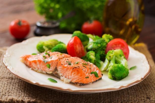 Pieczony łosoś rybny przyozdobiony brokułami i pomidorem. menu dietetyczne. menu rybne. owoce morza - łosoś.