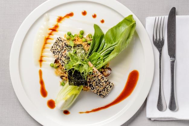 Pieczony łosoś sezamowy na podkładce ryżowej. widok z góry