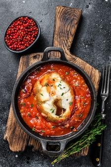 Pieczony morszczuk biała ryba z pomidorami na patelni. czarny stół. widok z góry.