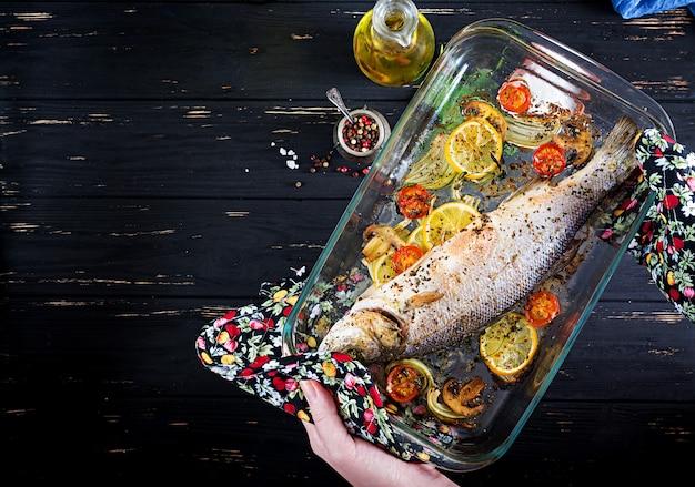 Pieczony okoń morski w naczyniu do pieczenia z przyprawami i warzywami do trzymania w rękach