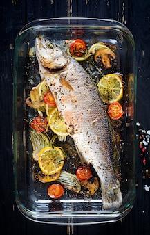 Pieczony okoń morski w naczyniu do pieczenia z przyprawami i warzywami