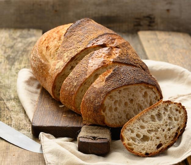 Pieczony okrągły chleb z białej pszennej deski na desce, bochenek pokrojony na kawałki, z bliska